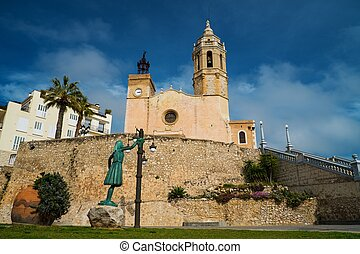 Statue of a woman against church of Sant Bartomeu i Santa Tecla in Sitges