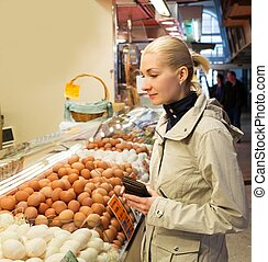 Young blond woman choosing fresh eggs on market