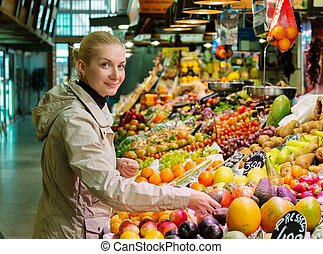 Young cheerful blond woman choosing fresh fruits on market