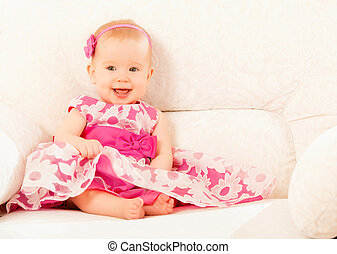 Beautiful pretty little baby girl in a pink dress sitting on the couch at home and smiling