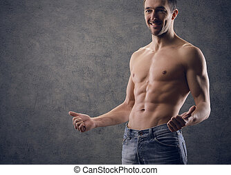 trained body wearing demim - Sexy muscular man thumbs up