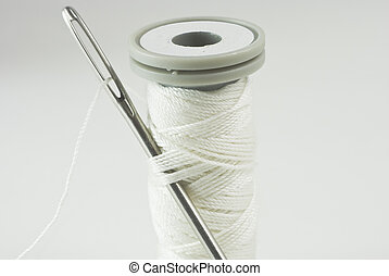 Needle and Cotton Reel - Sewing needle threaded with white...