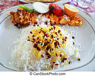An Iranian grilled chicken and tomatoes served on rice in...