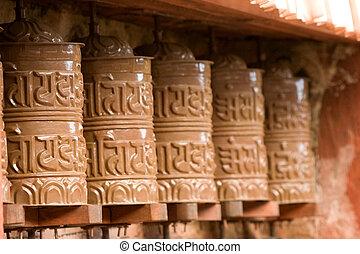 Buddhist Prayer Wheels - Row of brown, metal Buddhist prayer...