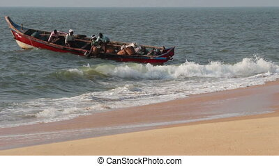fishermen unload fresh catch of fish on beach - Kerala India
