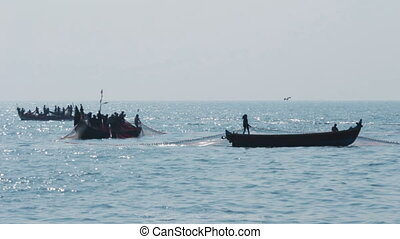 fishermen in boats pulling fishing nets - Kerala India