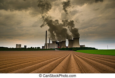 powerplant under a dramatic sky with a field in the...