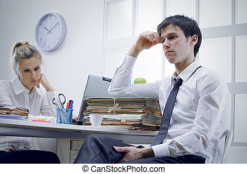 thoughtful - Two bored business people  in office