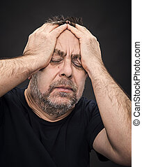 Headache. Man with face closed by hand