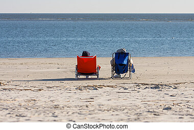 Orange and Blue Chairs on Beach - Two people resting in...