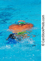 Swimmer under water in the pool, with bright sun