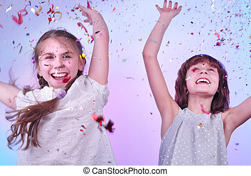 two girls having fun and dancing - studio portrait of two...
