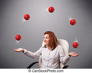 young girl sitting and juggling with red balls