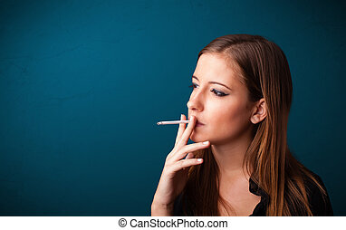 Beautiful woman smoking cigarette vith copy space -...