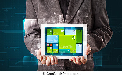Young businessman holding a tablet with modern software...