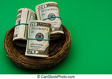 Nest Egg - Rolls of twenty dollar bills sitting in nest on...