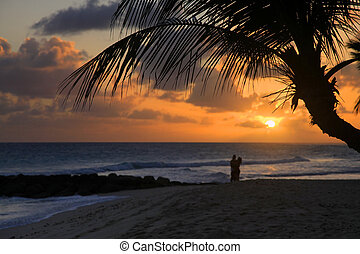 Romantic couple at beach with sunset in the background at...