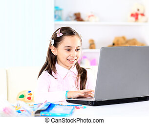 Cute little girl smiling and looking at laptop,Little girl...