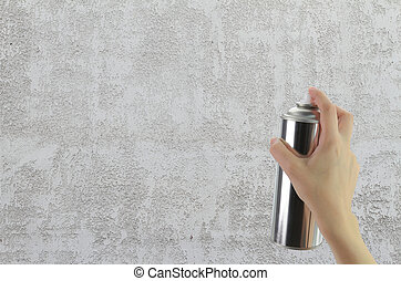 Human hand holding a graffiti Spray can in front of blank concrete wall