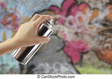Human hand holding a graffiti Spray can in front of a colorful wall