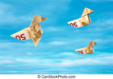 Bank note paper birds flying away on blue sky