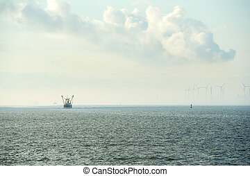 Industrial harbor with wind turbines and fishing boat -...