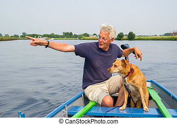 man in boat at the river - Man with dog in boat at the river