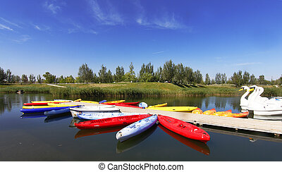 boats and canoes made of many colors on a quiet lake with...