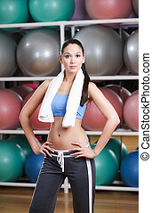 Sportive sexy woman in fitness gym with shelves of gym balls