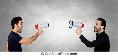 Two Young Men Shouting Through Megaphone In Front Of Each...