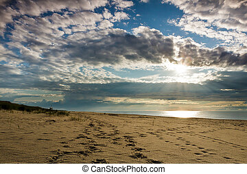 Footsteps on sand and dynamic sky over baltic sea