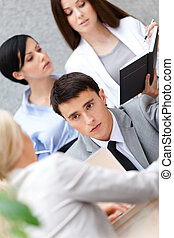 Businessman at the meeting with his pretty employees...