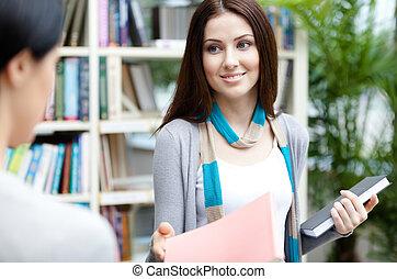 Undergraduate offers a book to her friend