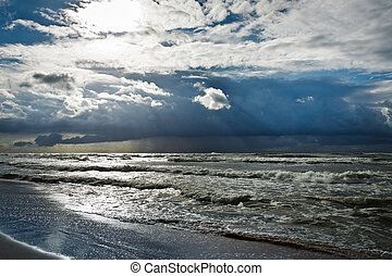 Storm over baltic sea with sunbeam