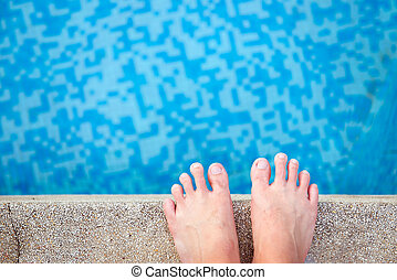 Swimming pool - View of bare male feet at swimming pool side