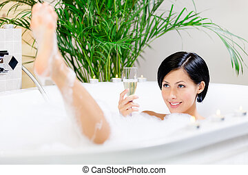 Girl taking a bath drinks sparkling wine - Woman taking a...