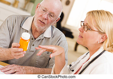 Doctor or Nurse Explaining Prescription Medicine to Senior...