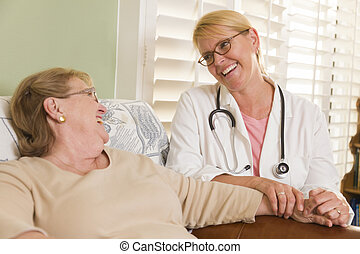 Doctor or Nurse Talking to Sitting Senior Woman - Happy...