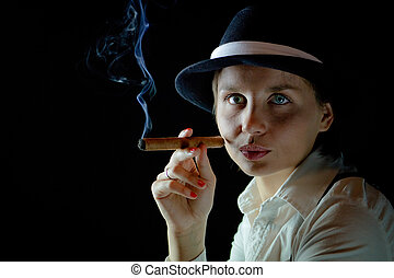 Woman in black hat with smoking cigar black  background isolated