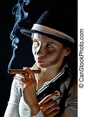 Woman in black hat with smoking cigar and gun black  background isolated
