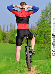 biker - mountain biker in spring landscape