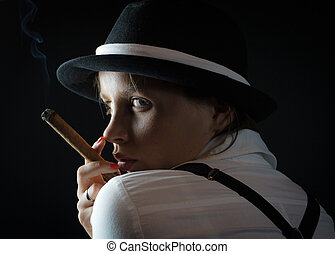 Woman in black hat with cigar in black isolated