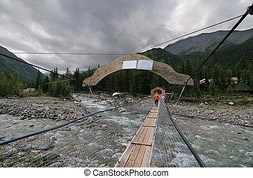 A pedestrian suspension bridge across mountain river
