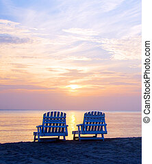 sunset on Picnic Center beach with lounge chairs and boats...