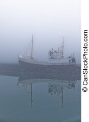 Fishing vessel in a foggy misty morning at Harbor