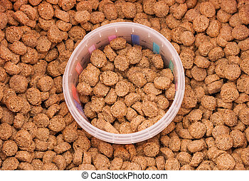 dry grained pets food with measured glass - dry brown...