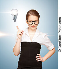 woman pointing her finger at light bulb - beautiful woman...