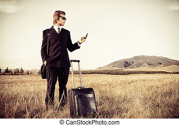 cell phone - Handsome business man standing in a field with...