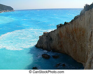 cliffs leading down to the blue sea on an island in greece
