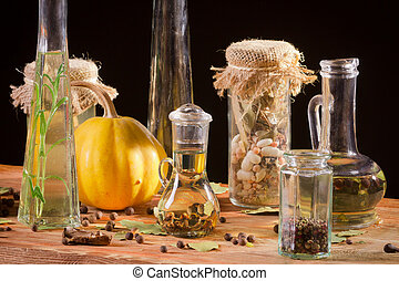 Spices and bottle of oil on wooden plank